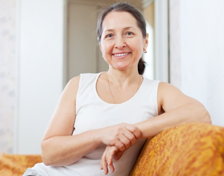 Smiling ordinary mature woman in home interior photo