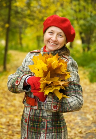 Portrait of senior woman  in autumn park photo