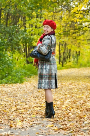 Happy mature woman  in coat walking outdoors in autumn photo