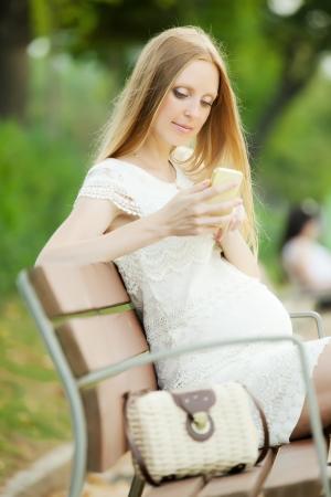 gravida:  pregnant woman using mobile in  summer park Stock Photo