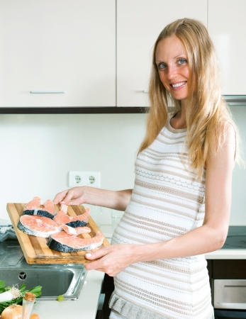 smiling pregnant woman cooks salmon in the kitchen photo