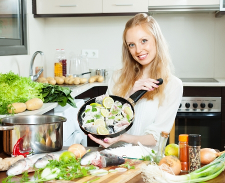 Smiling girl cooking fish in flour in frying pan at home kitchen  Stock Photo - 22642347