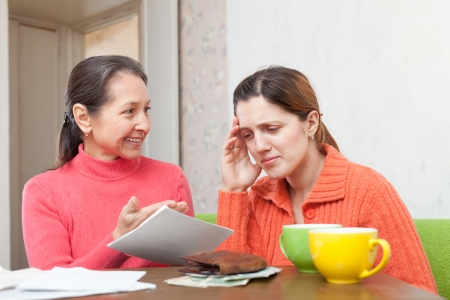 berate: mother berates adult daughter for bills or credits Stock Photo