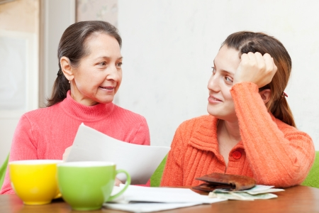 utility payments: Smiling mother helps adult daughter  to fills in  utility payments bills. Focus on mature