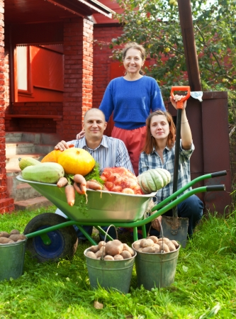 Man and two women with  harvest in vegetable garden photo