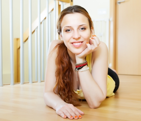 casualy: Happy girl lying on hardwood floor at home