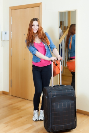 Cheeful red-haired woman with suitcase near door