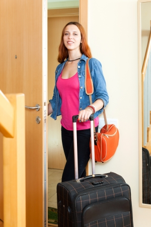 Cute positive young woman in jeans with luggage leaving the home photo