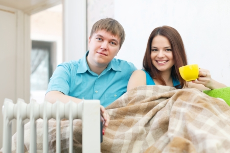 calorifer: Couple  relaxing at home near oil heater