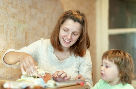 farcie: Happy mother with girl cookis in kitchen together. Focus on woman Stock Photo