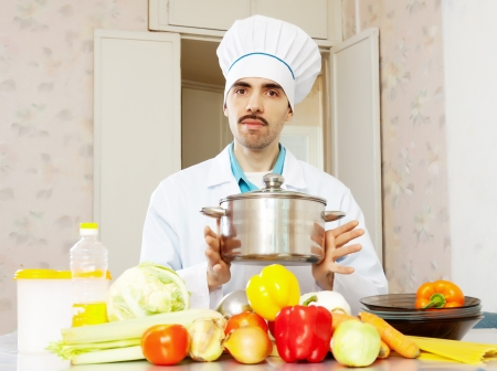 toque: Portrait of male cook in toque with pan  Stock Photo