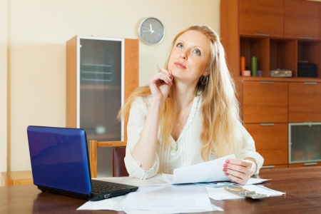 parsimony: pensive long-haired woman reading financial documents at home Stock Photo