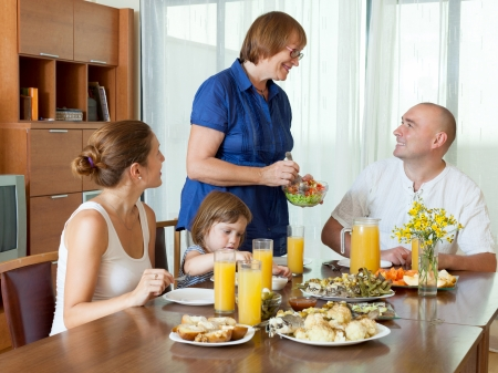 celebratory: Portrait of happy smiling three generations family together around festive table