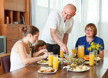 Happy three generations family eating fish over  table at home interior photo