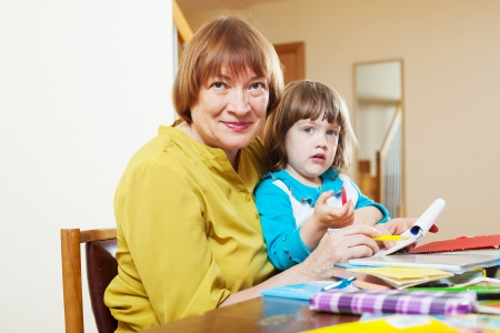 Mature woman and baby girl drawing with colored pencils in home photo