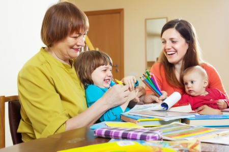 Happy mature woman playing with daughter and grandchildren at table photo