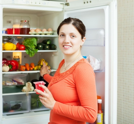Young woman near fridge at home photo