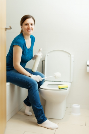 woman cleaning toilet bowl with brush  photo