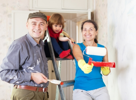 Happy family of three makes repairs at home photo