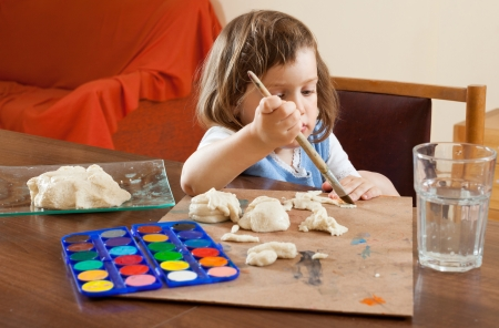 The child learns to paint the dough figurines in the room photo