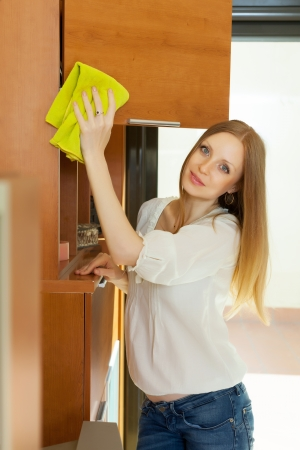 long-haired woman cleaning wooden furniture at home photo