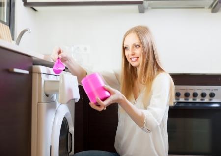 Smiling blonde woman putting whitener in to washing machine  Banco de Imagens