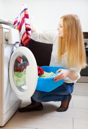 blonde woman loading the washing machine. Cleaning and Laundry photo