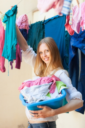 hangs: Smiling woman hangs clothes to dry on clothes-line Stock Photo
