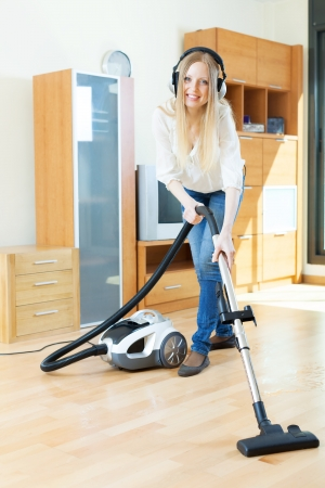 Happy long-haired woman in headphones cleaning with vacuum cleaner  photo