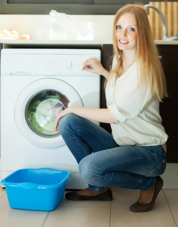 Home laundry. Blonde long-haired woman using washing machine at home photo