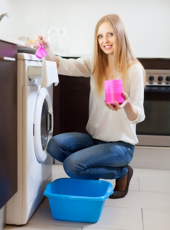 Smiling blonde woman using washing machine with laundry detergent at home photo