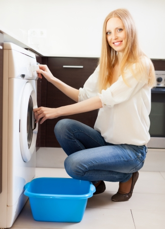Cheerful long-haired woman doing laundry at her home photo