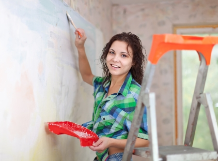 Happy woman paints wall with brush at home photo