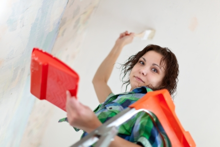 girl paints ceiling with brush at home photo
