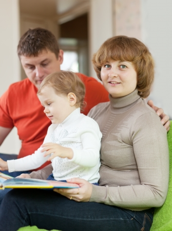 Happy parents with  child in home interior. Focus on  mother Stock Photo - 23162620