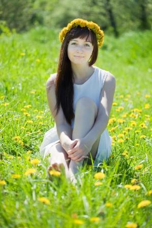 girl sitting outdoor in dandelion wreath photo