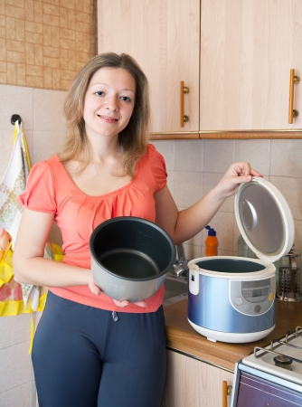 slow cooker: Young woman with electric slow cooker in  kitchen Stock Photo
