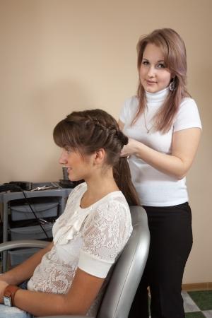 hairtician: hair stylist works on woman hair in salon Stock Photo
