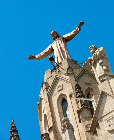 cor:  Sculpture of Jesus on top of Temple of Sagrat Cor at Tibidabo in  Barcelona, Spain