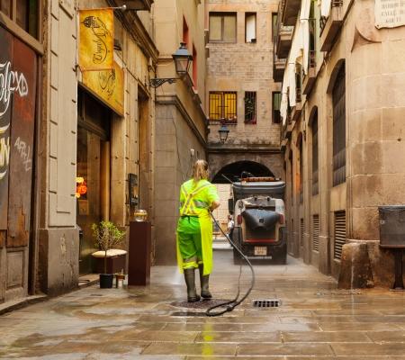 recolector de basura: BARCELONA, ESPAÑA - 01 de junio: La limpieza en húmedo de las calles viejas en 01 de junio 2013 en Barcelona, ??España. Barrendero limpiando barrio antiguo con agua