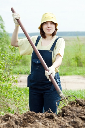 The woman scatters the manure pitchfork in the field Stock Photo