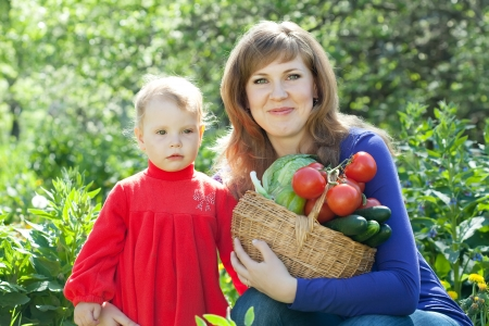 Happy woman and baby with vegetables harvest in garden photo