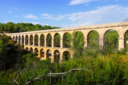 acueducto: ancient roman aqueduct in summer forest. Tarragona,  Spain Stock Photo