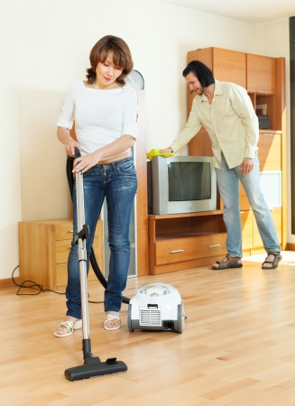 amicable woman and man doing housework together in home photo