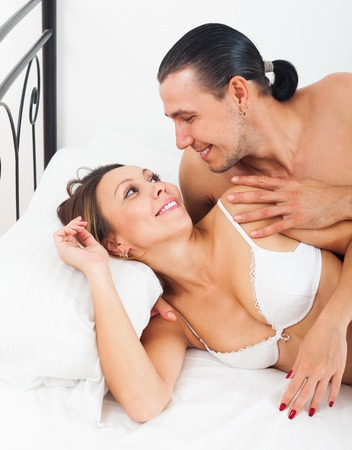 Loving couple in bed in bedroom photo