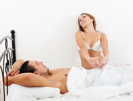 Loving middle-aged couple awaking together on bed in home interior photo