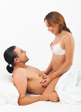 Smiling couple in bed in bedroom photo