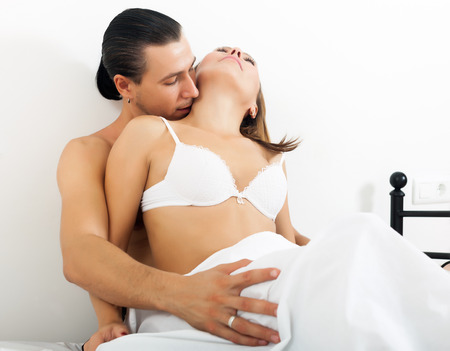 Man kissing girl in neck at bed   photo