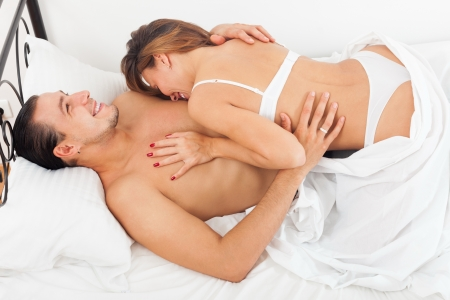 Smiling lovers in bed in bedroom photo