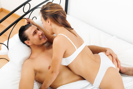 Handsome man having sex with woman on white sheet in bed   photo
